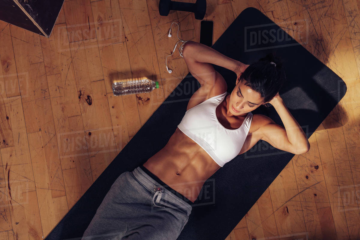 Sporty Young Woman Lying On Yoga Mat Doing Sit Ups In D2012 56 056
