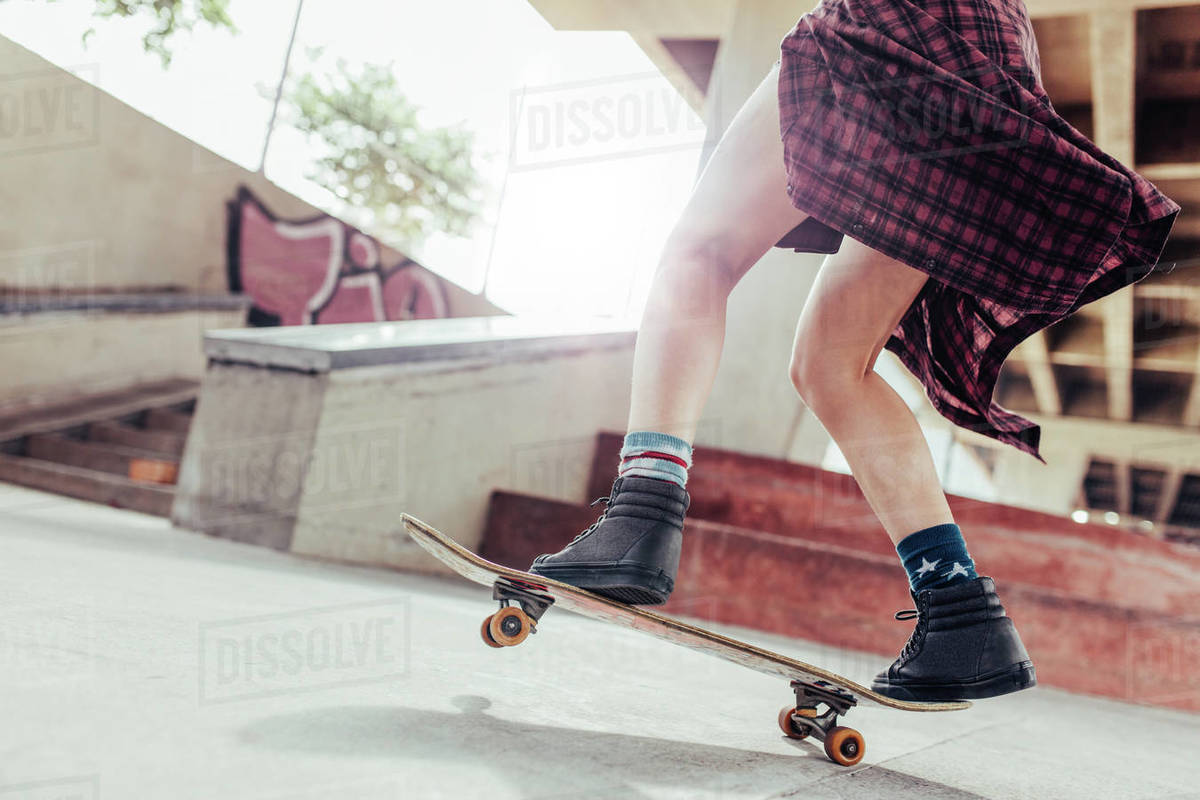 Low angle shot of young woman legs skateboarding at skate park Royalty-free stock photo