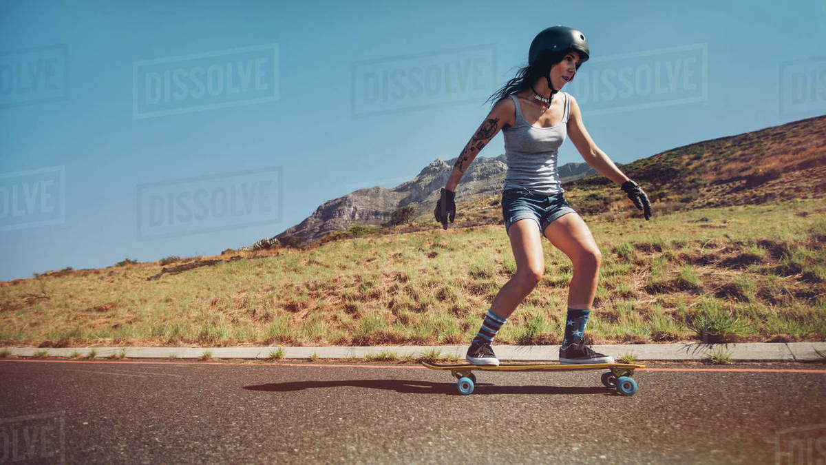 Young woman skateboarding down a road. Female skateboarder wearing helmet skating on rural road. Royalty-free stock photo
