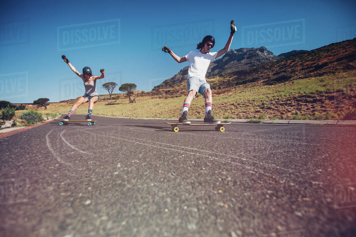 Young man and woman skateboarding on the road. Young couple practicing skating on a open road. Royalty-free stock photo