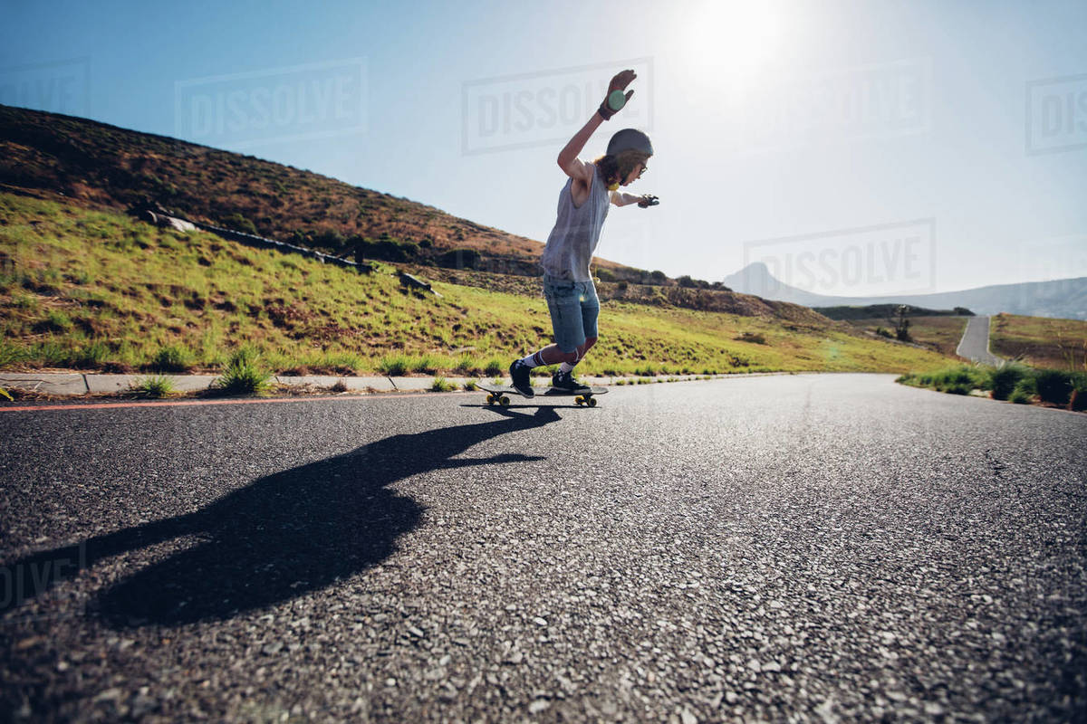 Outdoors shot of young man skateboarding down the road on sunny day. Royalty-free stock photo