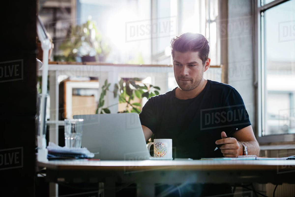 Shot Of Handsome Young Man Sitting At His Desk Looking At Laptop And Writing Notes Businessman Working In His Office Stock Photo