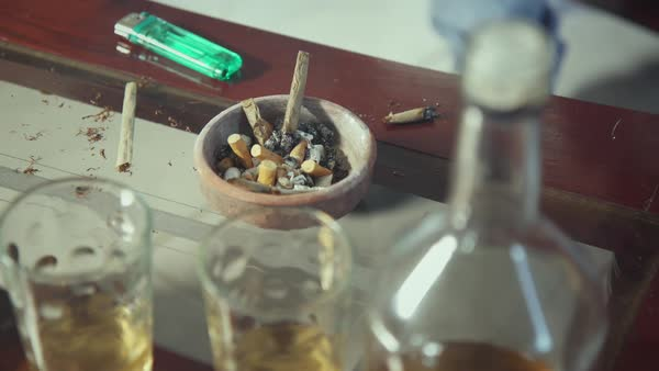 Liquor bottle and glasses, ashtray with cigarette butts, hashish joints on table at home Royalty-free stock video