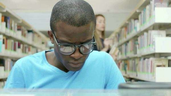Male black college student reading book in school library, with caucasian woman taking book from shelves in background. Dolly shot Royalty-free stock video