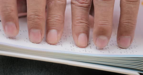 Visually impaired man reading book with hands, touching page written in Braille language with fingers. Close-up Royalty-free stock video