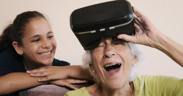 Happy old woman using virtual reality helmet with little girl at home Royalty-free stock video