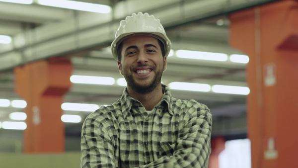 Portrait of happy young man employed in logistics facility smiling at camera, people working in warehouse, workers in industry. Royalty-free stock video