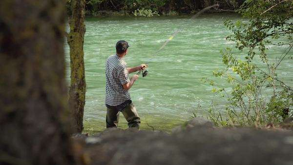 Man on vacation, relaxing and fishing near river in forest Royalty-free stock video
