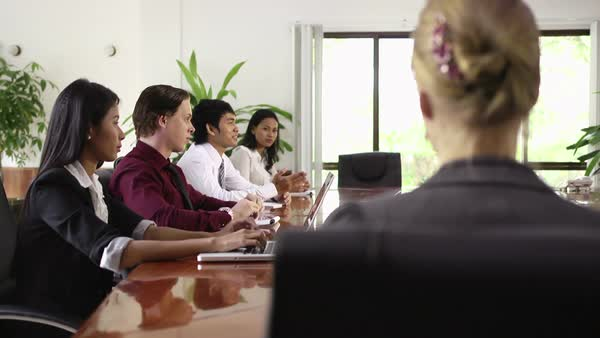 Beautiful young blonde woman working as manager and smiling at camera during business meeting with colleagues. Rack focus Royalty-free stock video