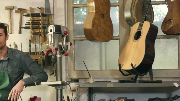 Portrait of Italian adult man working as craftsman in shop with tools, bass, guitar and musical instruments Royalty-free stock video