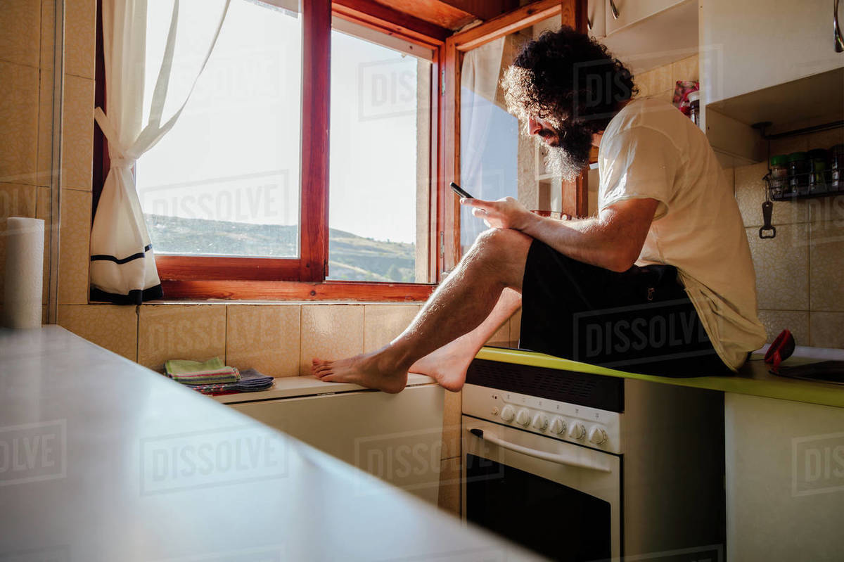 Young man having breakfast and using his smartphone near window in the confinement at home due to the coronavirus Royalty-free stock photo