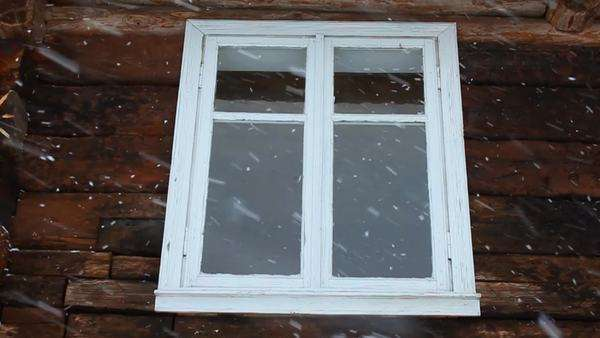 Slow motion of snowing against the window of an old wooden house background Royalty-free stock video
