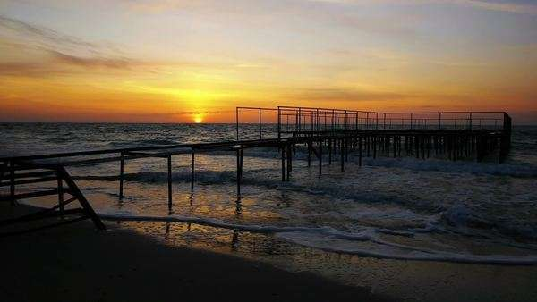 Amazing yellow and orange sky after sunrise reflected on wet sandy beach with a pier on background Royalty-free stock video