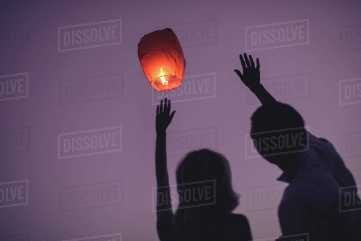 Silhouettes Of Couple Waving Hands To Flying Chinese Lantern In Violet Evening Sky Stock Photo Dissolve