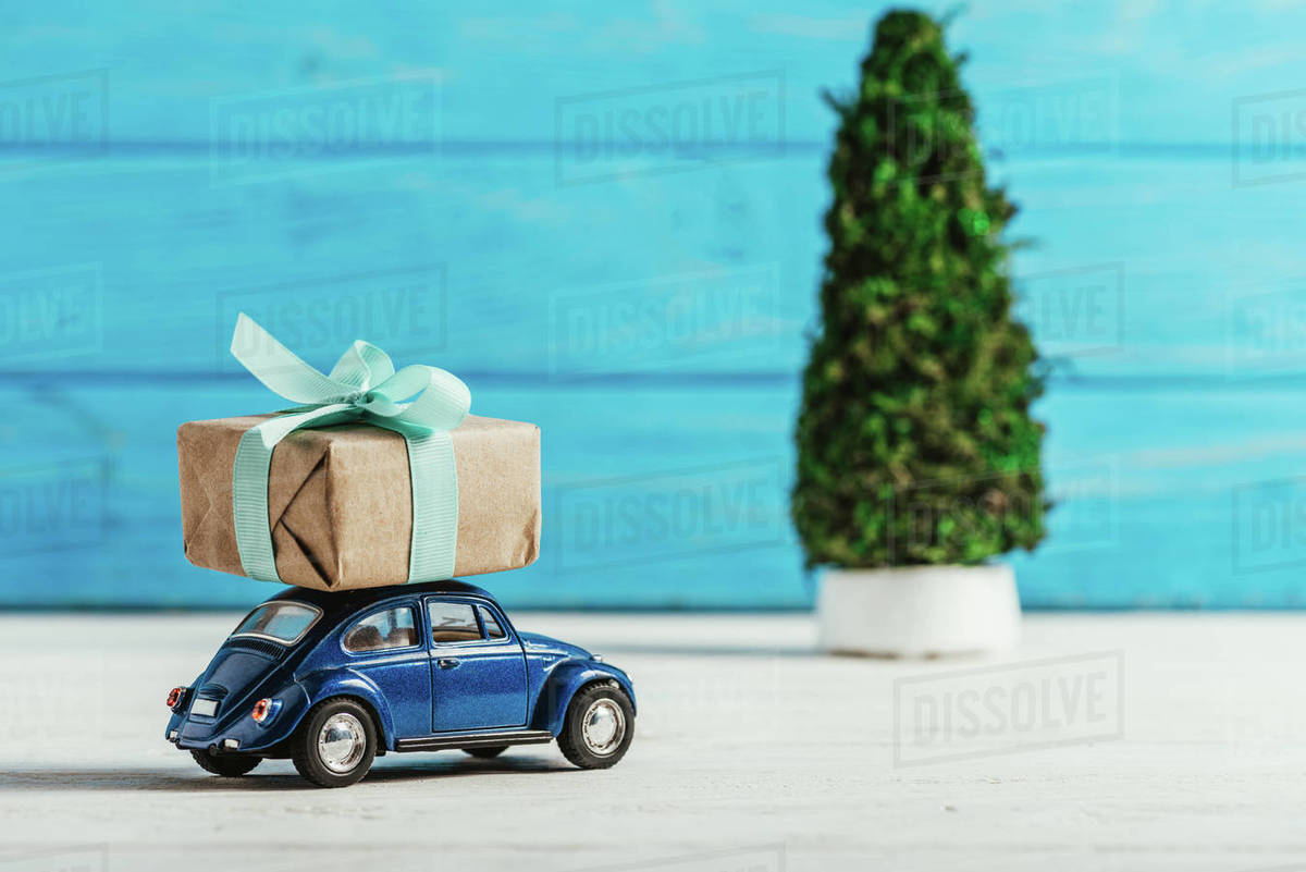 Car Christmas Tree.Close Up Shot Of Toy Car With Gift Box And Miniature Christmas Tree On Blue Wooden Background Stock Photo