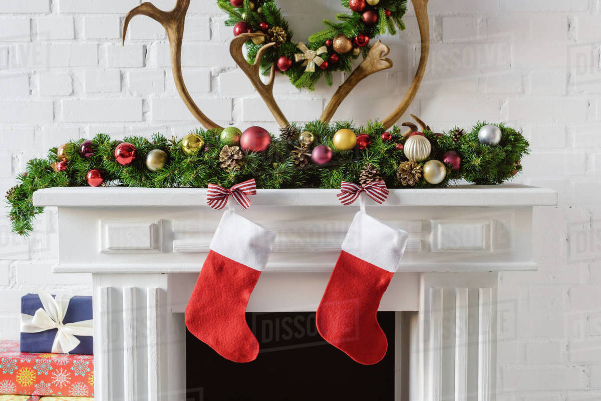 Christmas wreath with decorations, stockings and deer horns over fireplace mantel