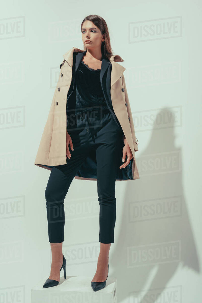 quality design 9ab4b 5046f elegant girl posing in black suit and classic trench coat, on grey stock  photo