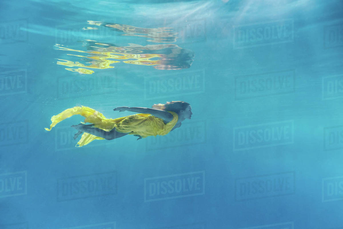 f184e0520d Underwater picture of beautiful young woman in dress swimming in swimming  pool