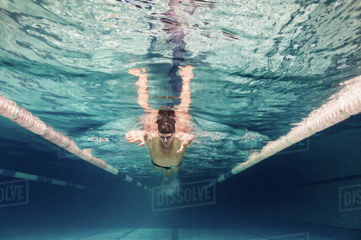Underwater picture of young swimmer in cap and goggles training in swimming  pool stock photo