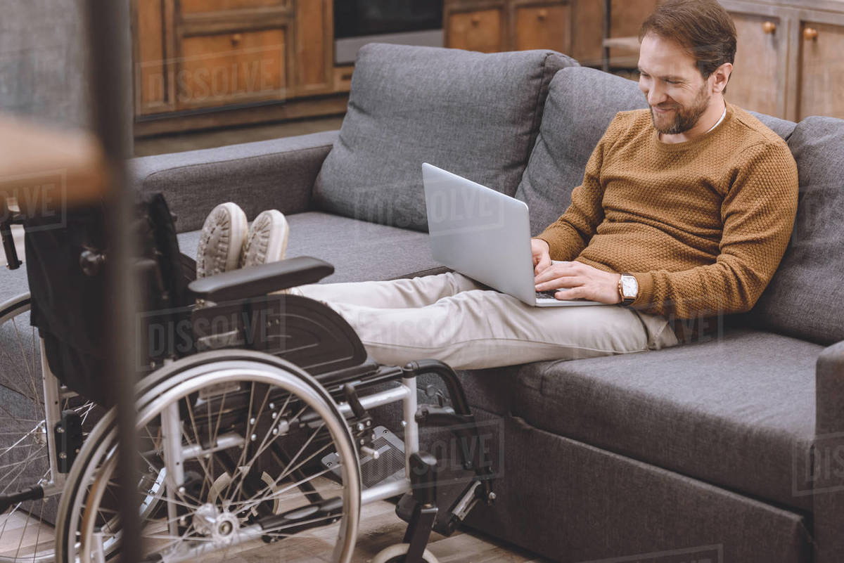 Super Smiling Disabled Man Putting Legs On Wheelchair While Using Laptop On Sofa At Home Stock Photo Theyellowbook Wood Chair Design Ideas Theyellowbookinfo