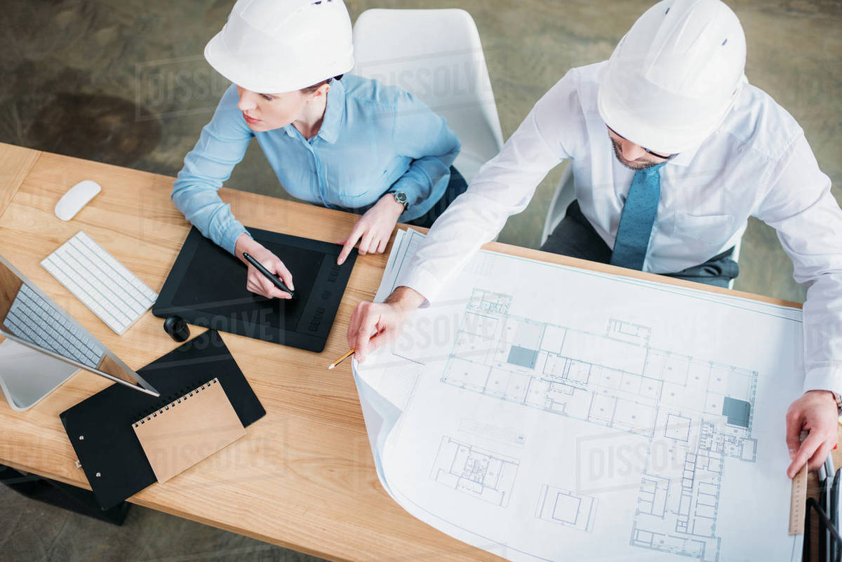 High angle view of architects working with building plan and drawing tablet at office Royalty-free stock photo