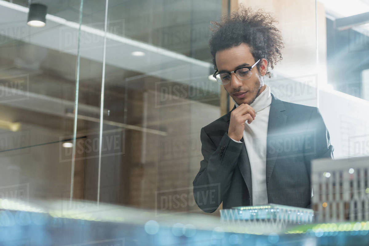 Thoughtful young architect in suit near buildings miniature model at office Royalty-free stock photo