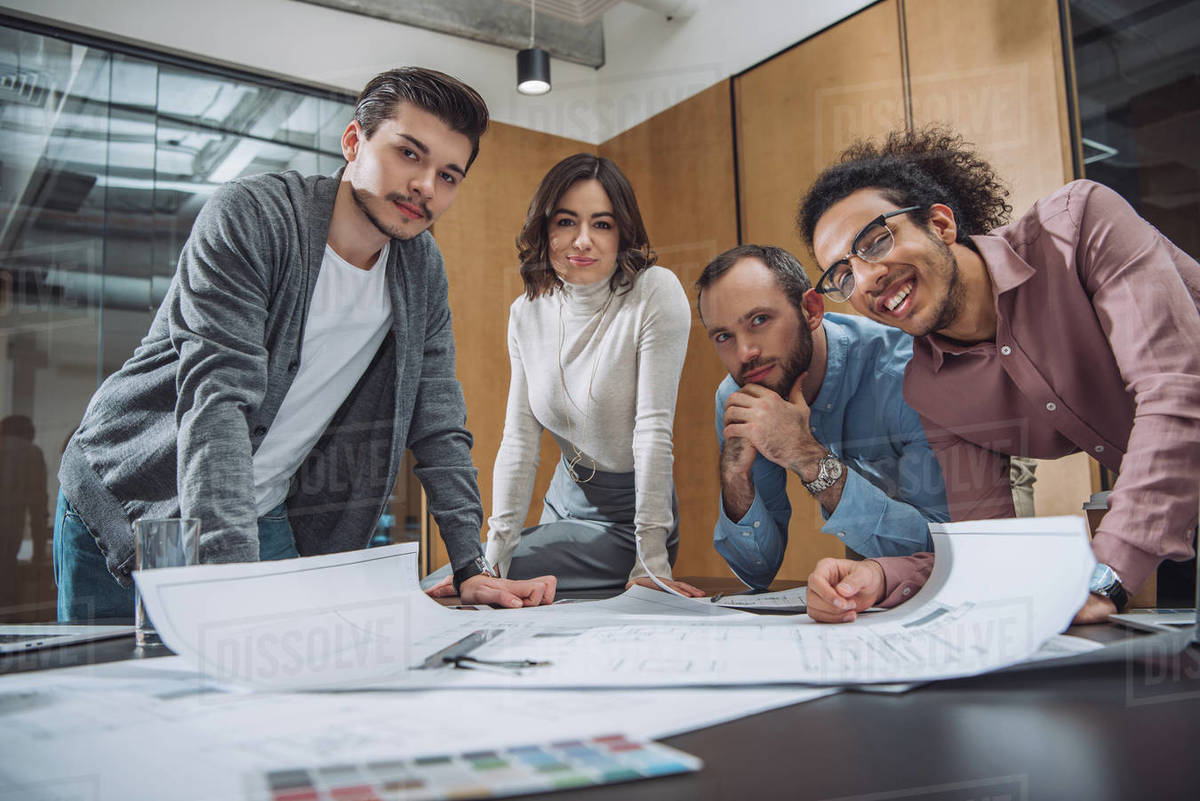 Group of successful architects discussing plans and looking at camera at office Royalty-free stock photo