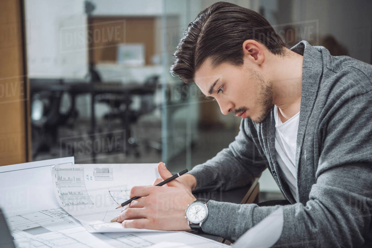 Handsome young architect drawing building plans at office Royalty-free stock photo