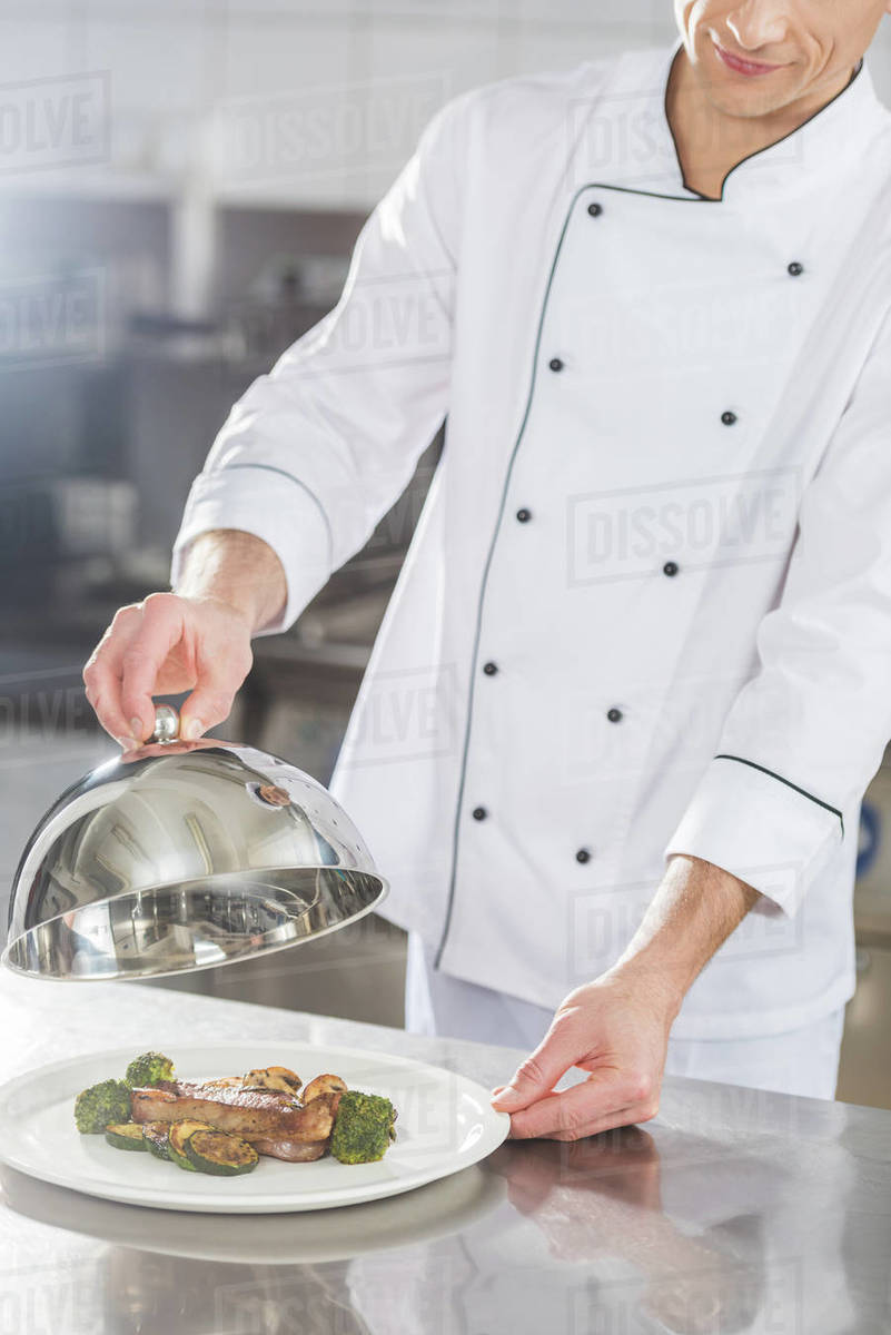 Cropped image of chef covering plate with lid at restaurant kitchen - Stock  Photo - Dissolve
