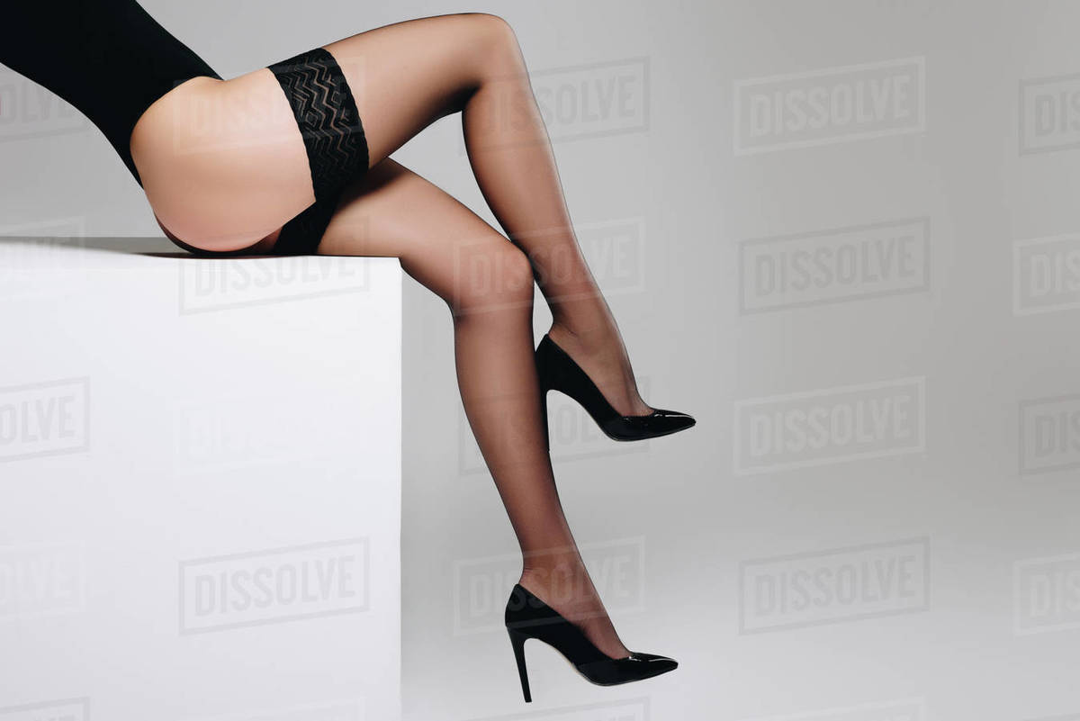 4fb3c331c36 Sensual woman in black nylon stockings sitting on white box isolated on grey