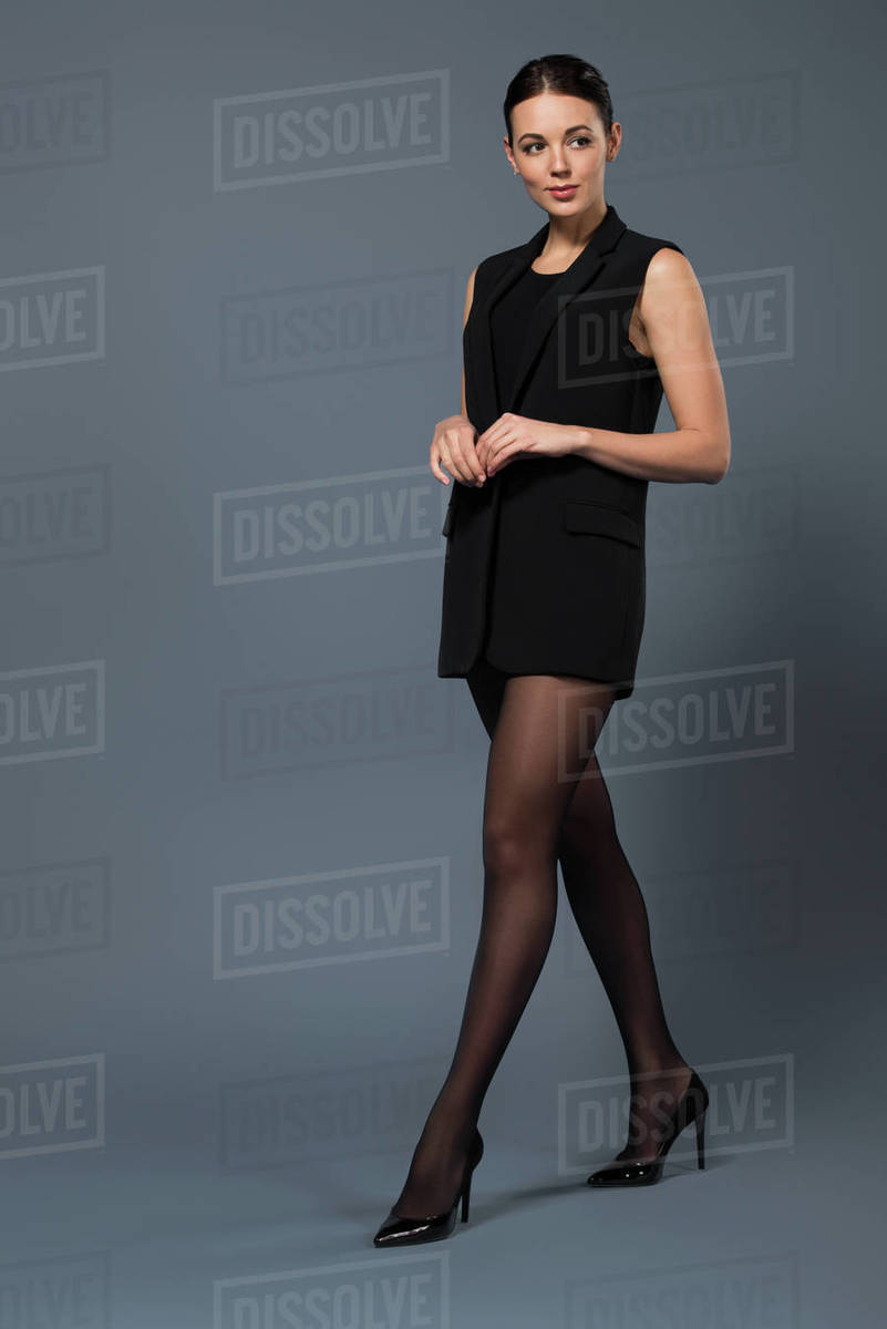 Attractive woman in black pantyhose and vest on dark background ...