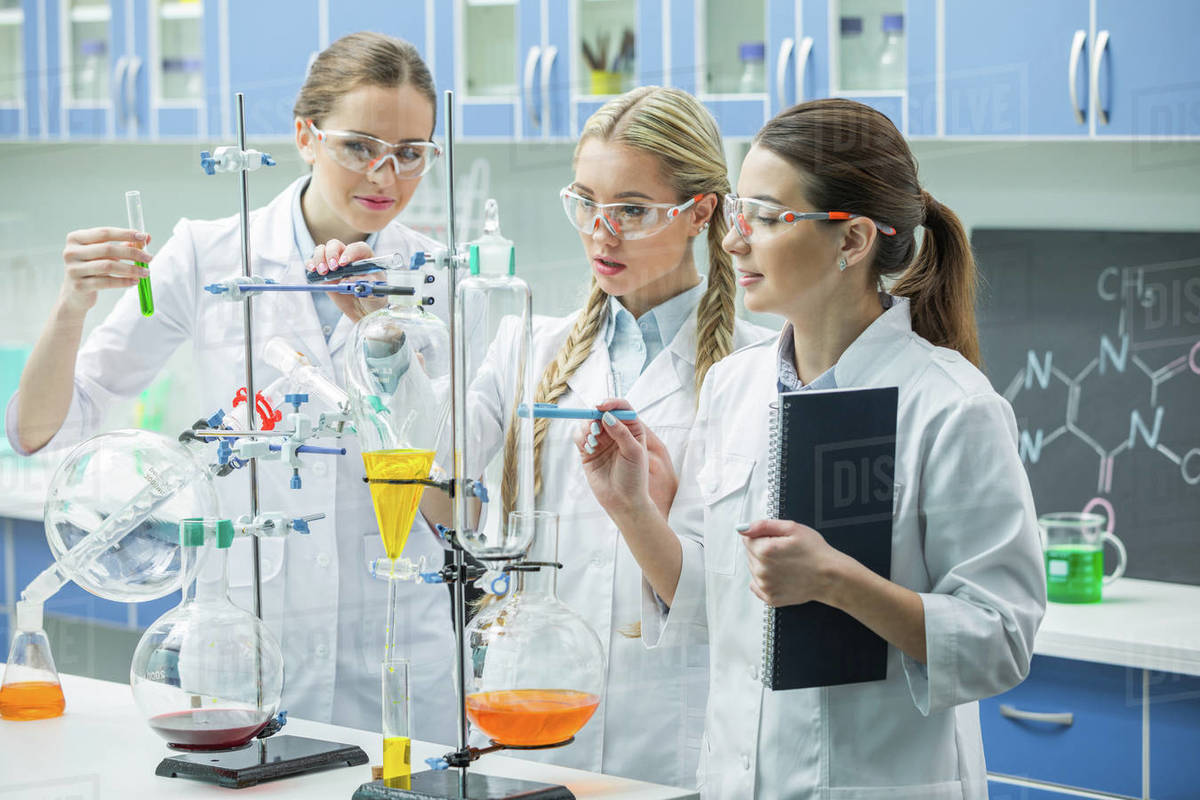 Young female scientists in lab coats making experiment in chemical  laboratory - Stock Photo - Dissolve