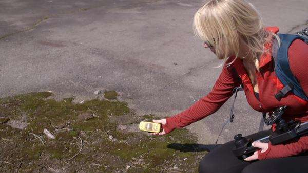 Medium shot of woman measuring ionizing radiation on ground Rights-managed stock video