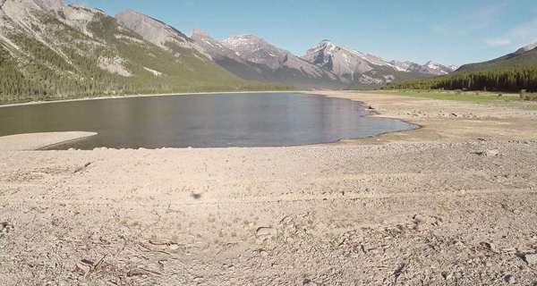 Very wide shot of a drone lifting off a lake shore in Spray Lakes Royalty-free stock video