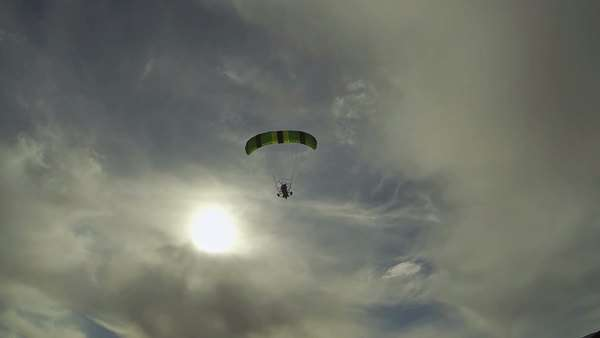 Aerial ultralight powered parachute flying into hazy sun Low level Ultralight flight over rural community and farms. Airborne powered parachute having fun with extreme recreation. Royalty-free stock video