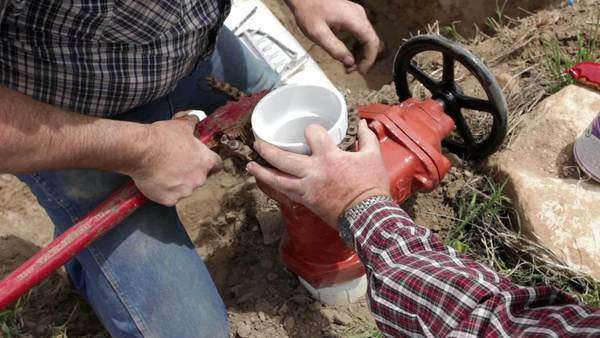 Plumber and farmer fixes and repairs large irrigation water pipe valve in a deep trench. & Backhoe industrial front loader backhoe push dirt into farm trench ...