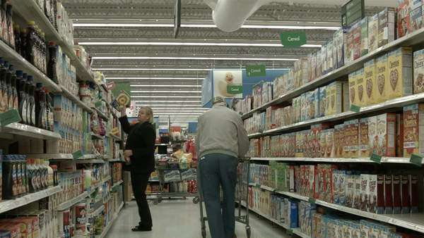 Woman shopping in breakfast cereal section store POV Thanksgiving and Christmas shopping in Walmart grocery and