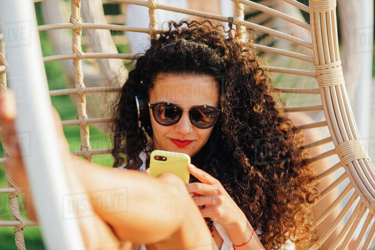 Portrait of a young woman with curly hair and sunglasses at a wooden swing chair relaxing and listening to music thru a smartphone in the resort near to pool. Royalty-free stock photo