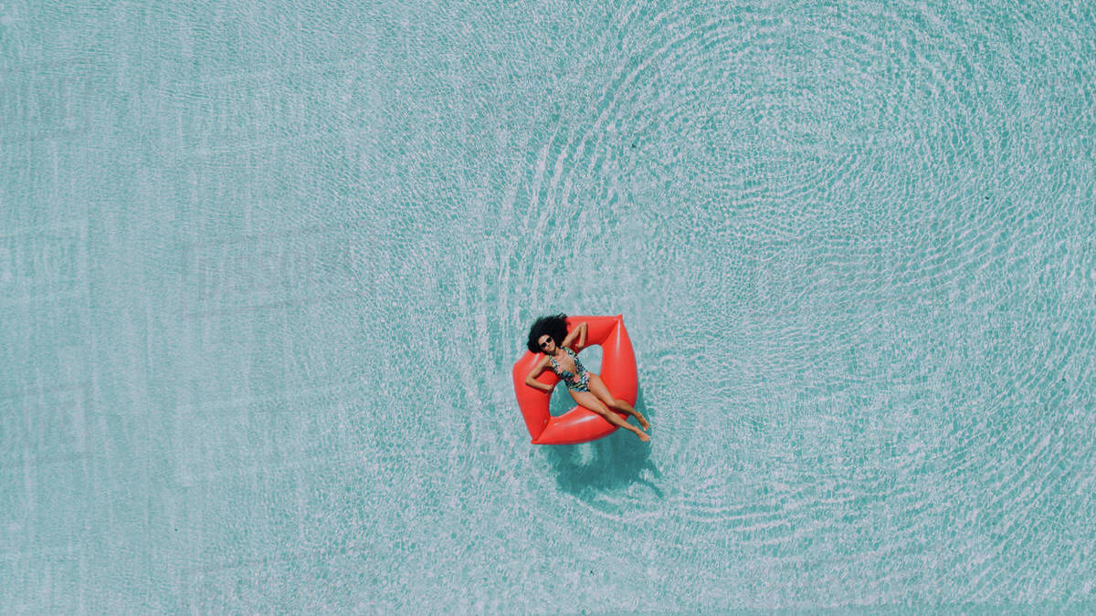 Woman relaxing on big red floating mattress in lips shape in the pool water on hot sunny day. Female enjoying summer holidays. Top view. Royalty-free stock photo