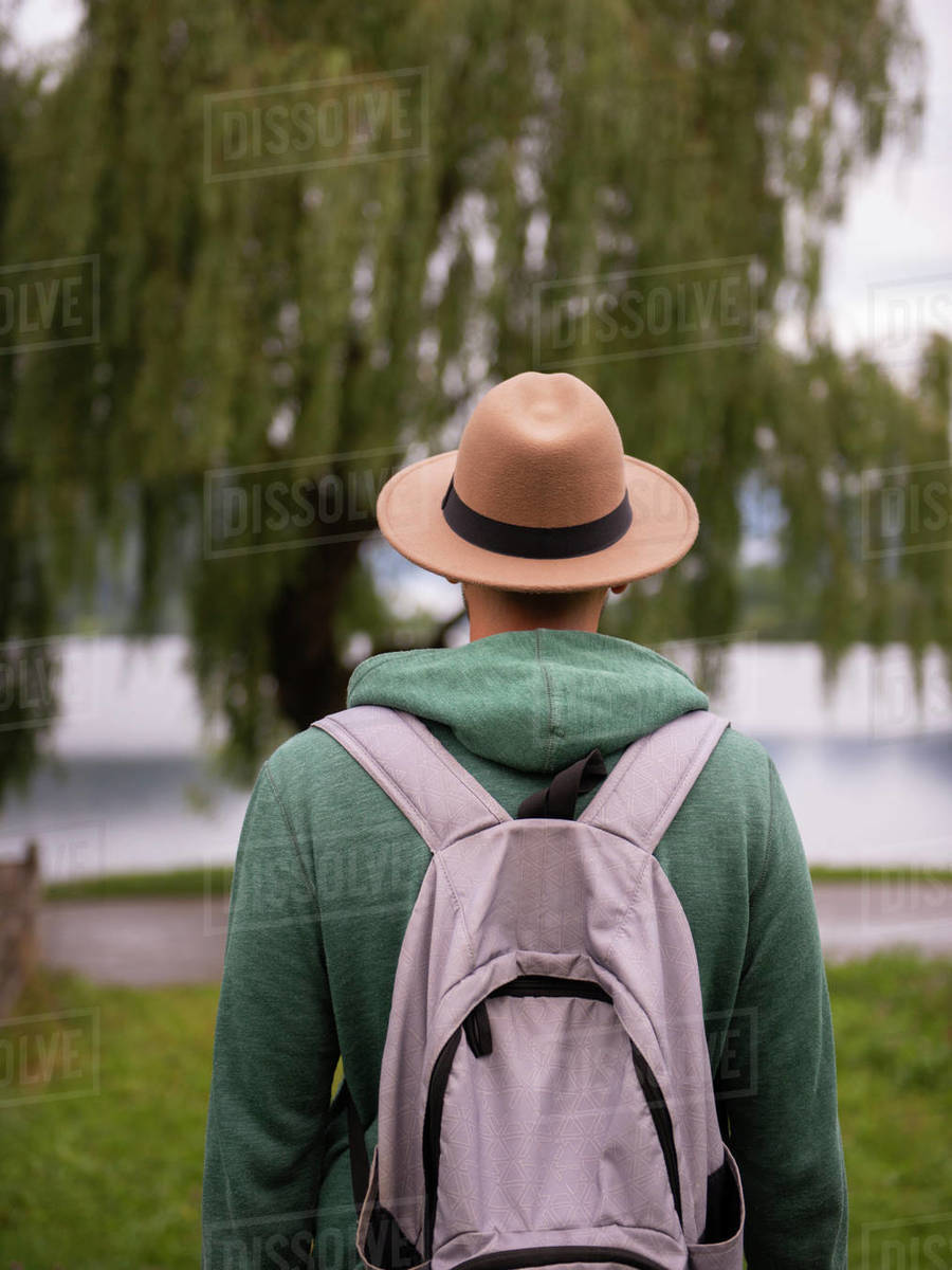 Back view of man in brown hat standing and looking at lake  Royalty-free stock photo