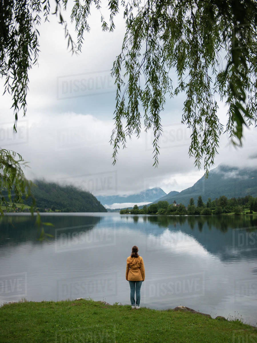 Back view of woman standing at lake shore and looking at water Royalty-free stock photo
