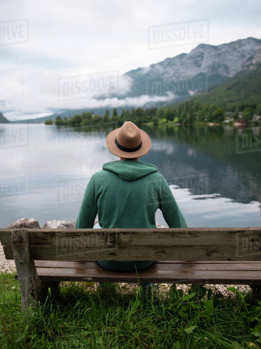 Back view of man sitting on bench and looking at lake  Royalty-free stock photo
