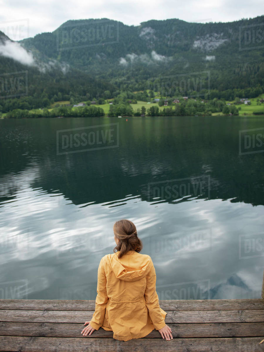Back view of woman sitting on wooden pier and enjoying the lake view Royalty-free stock photo