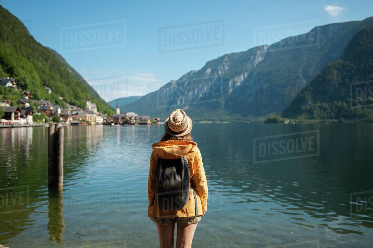 Woman with backpack standing at lake shore and enjoying the scenic view Royalty-free stock photo