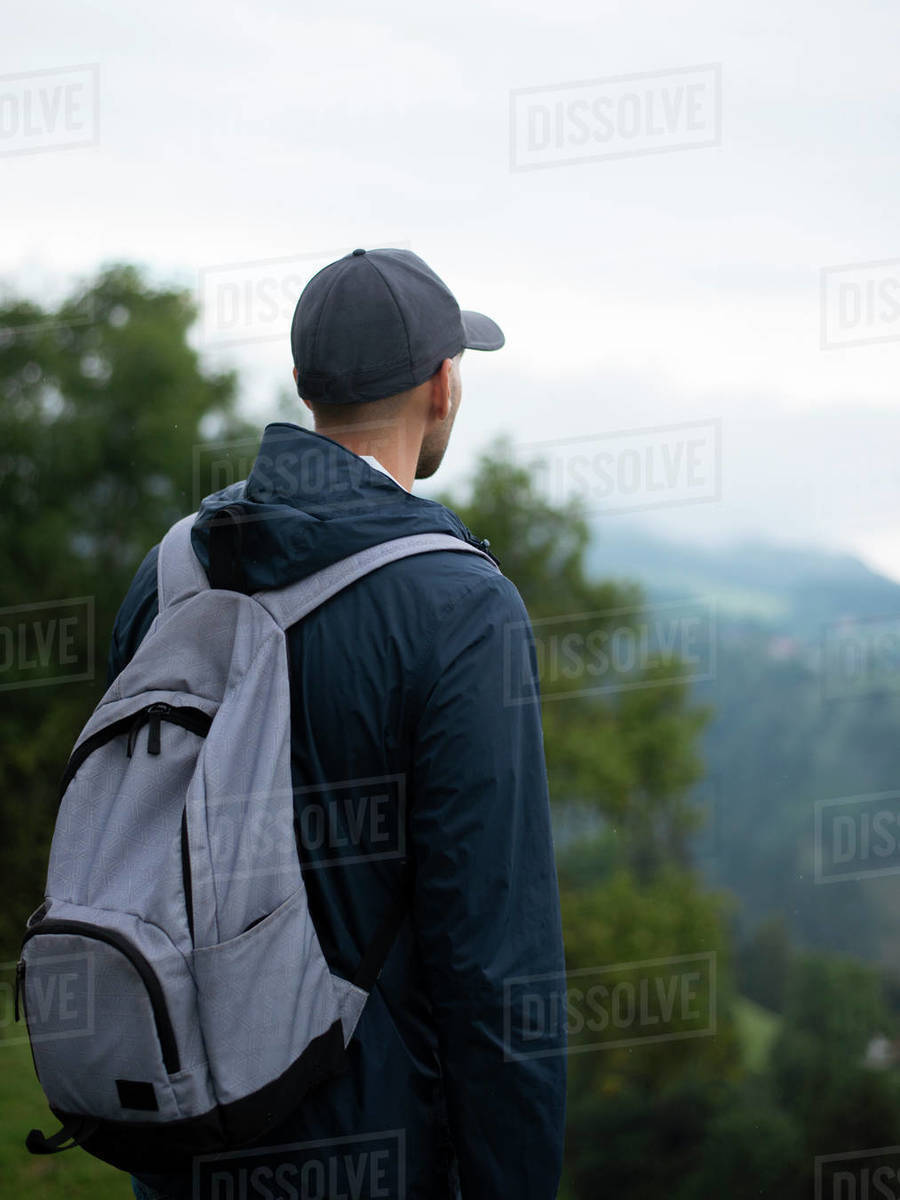 Back view of man with backpack standing in forested mountains and enjoying the view Royalty-free stock photo