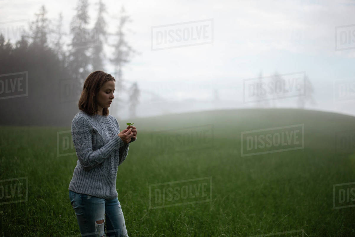 Woman standing in field holding three leaf clover Royalty-free stock photo