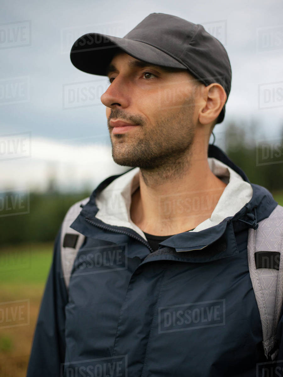 Male backpacker standing in field and looking away against cloudy sky Royalty-free stock photo