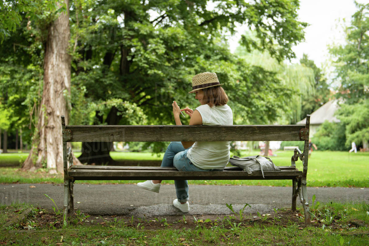 Woman sitting on bench in park messaging on cell phone Royalty-free stock photo