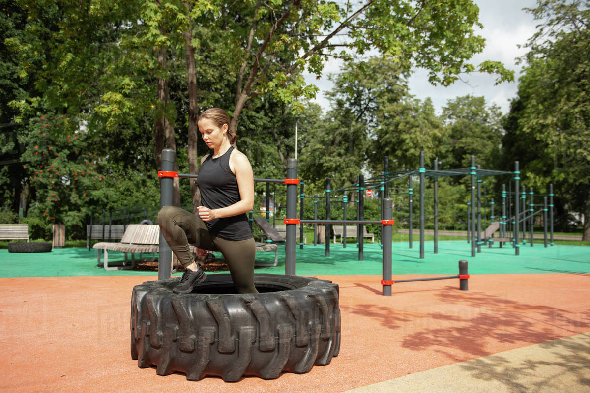 Fit female athlete exercising with big tire outdoors  Royalty-free stock photo