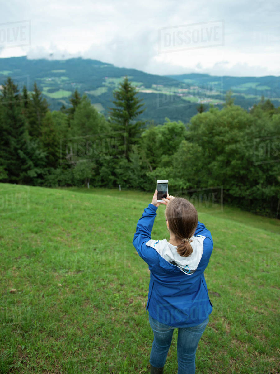 Woman photographing by smart phone forested mountains in fog Royalty-free stock photo